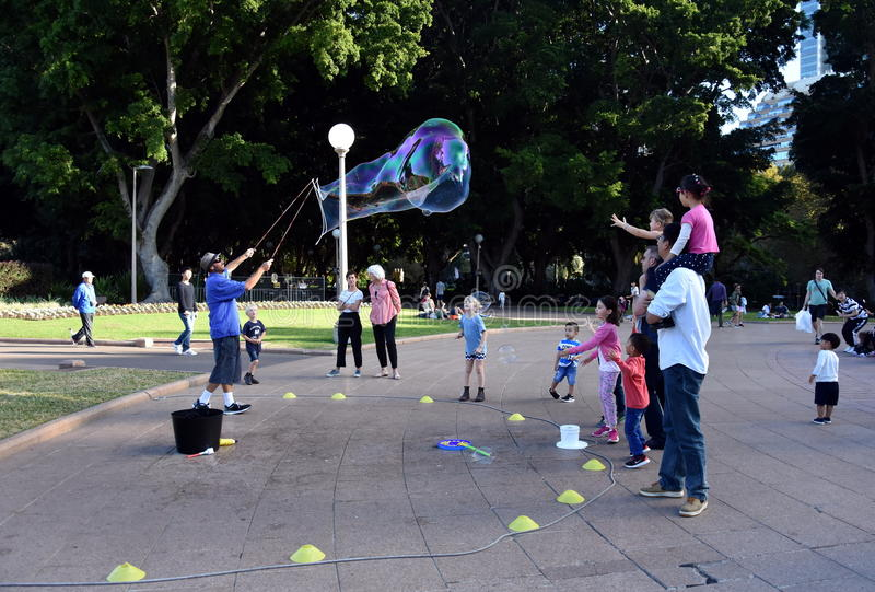Kids catching and having fun and with soap bubbles stock image