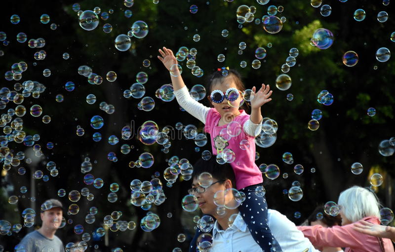 Kids catching and having fun and with soap bubbles stock photos
