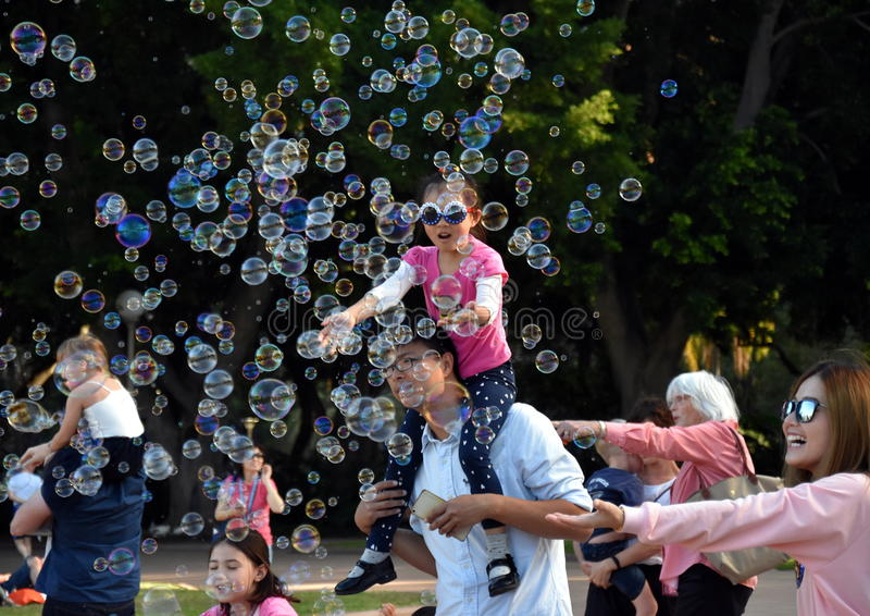 Kids catching and having fun and with soap bubbles royalty free stock images