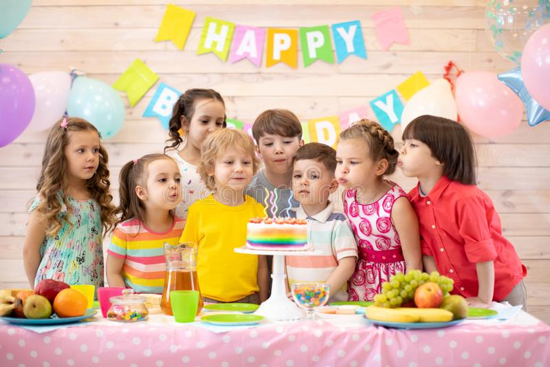 Kids celebrate birthday party and blow candles on festive cake stock photos
