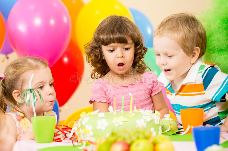 Kids celebrate birthday party blowing candles royalty free stock image