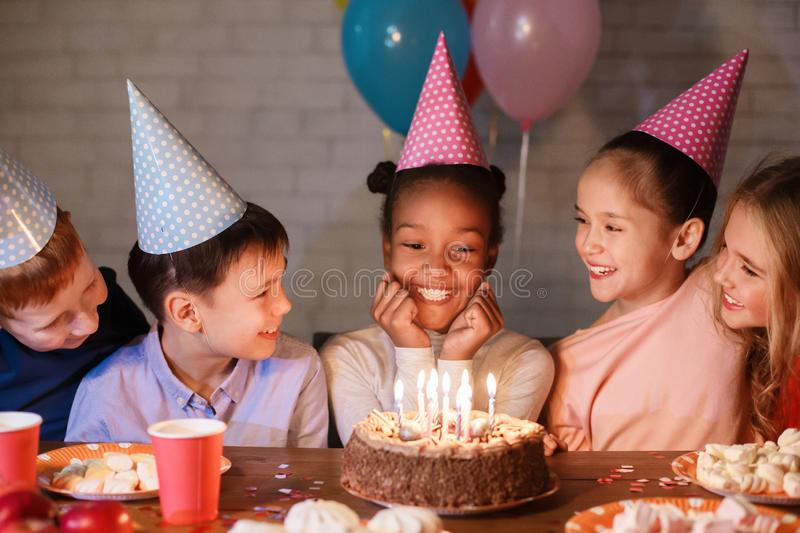 Kids celebrating birthday, looking at cake with candles royalty free stock images
