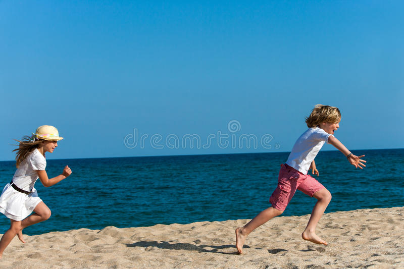 Kids chasing each other. Two kids running after each other on beach stock photos