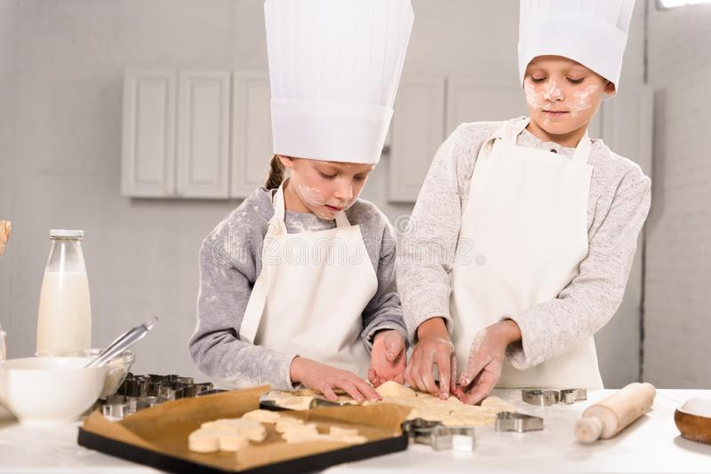 Kids in chef hats and aprons cutting out dough for cookies at table. In kitchen royalty free stock image