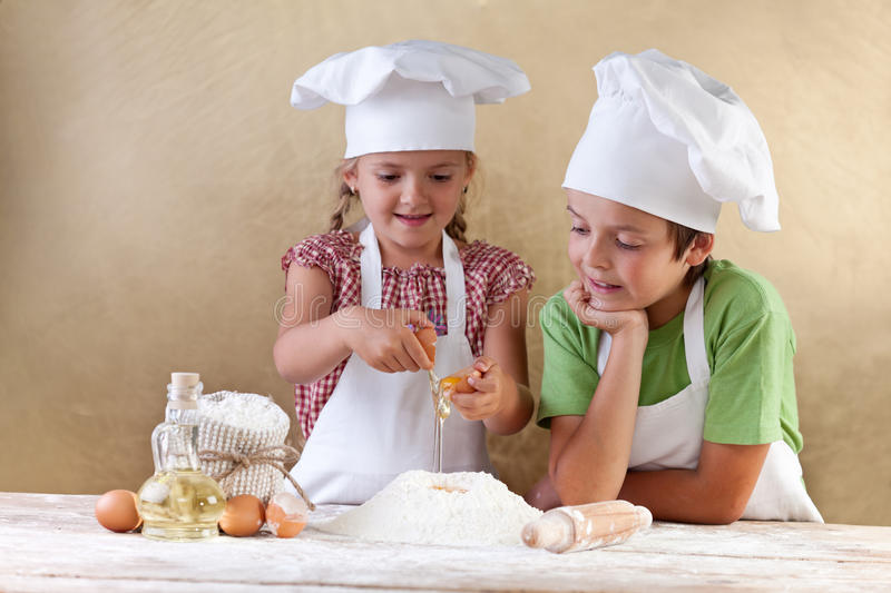 Kids with chef hats preparing tha cake dough. Mixing ingredients stock photography