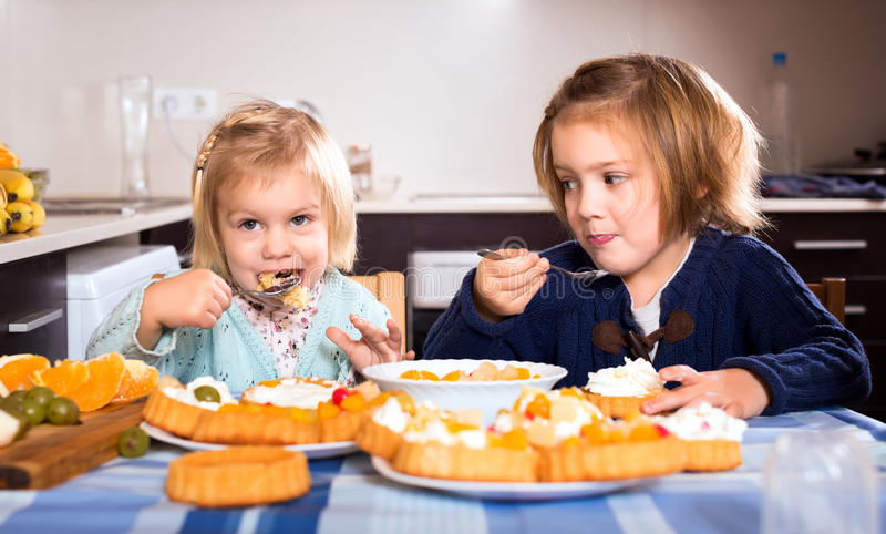 Kids chewing cakes. Young girls eating delicious cakes with cream with spoons in the kitchen. Putting cakes in their mouth and chewing stock images