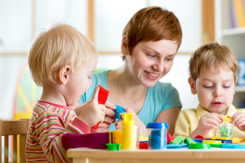 Kids or children and mother play colorful clay toy. Mother teaches her children to work with colorful play clay toys stock photo