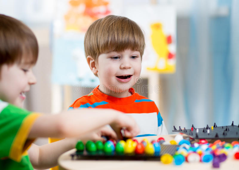 Kids children playing mosaic game in kindergarten room royalty free stock photos