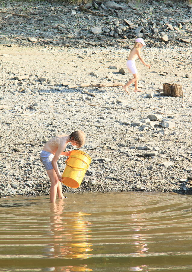 Kids cleaning a lake. Little barefoot girl and boy in shorts cleaning water of a lake by yellow barrel royalty free stock photo