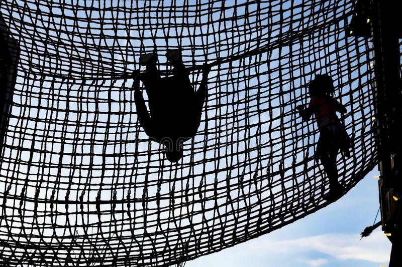 Kids climbing inside a rope net high in the sky - girl walking and boy hanging upside down - silhouettes royalty free stock image