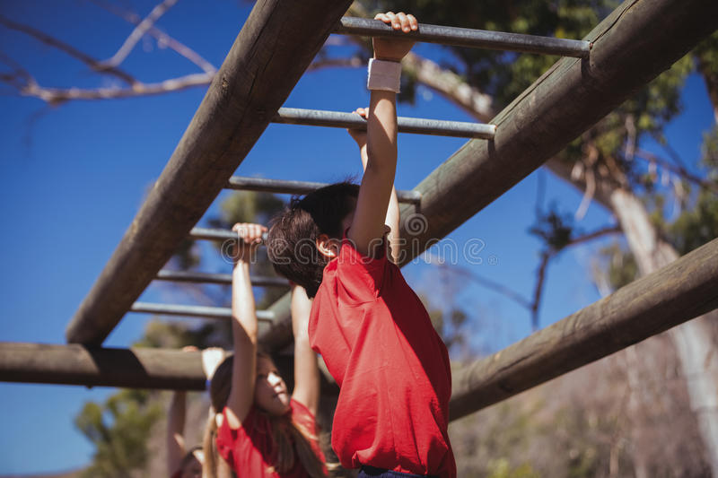 Kids climbing monkey bars during obstacle course training stock photography