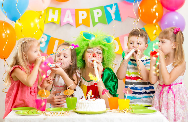 Kids and clown celebrate birthday party. Kids and clown at birthday party royalty free stock image