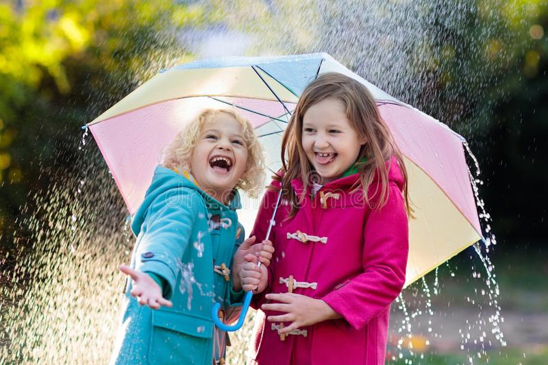 Kids with umbrella playing in autumn shower rain. Kids with colorful umbrella playing in autumn shower rain. Little boy and girl in warm duffle coat play in a stock photos