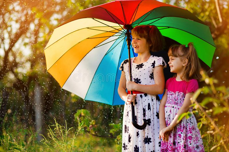 Kids with colorful umbrella playing in autumn shower rain. Little girls play in park by rainy weather. Fall outdoor fun for children. Kid catching rain drops royalty free stock photo