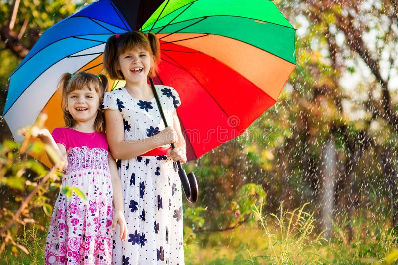 Kids with colorful umbrella playing in autumn shower rain. Little girls play in park by rainy weather. Fall outdoor fun for children. Kid catching rain drops royalty free stock image