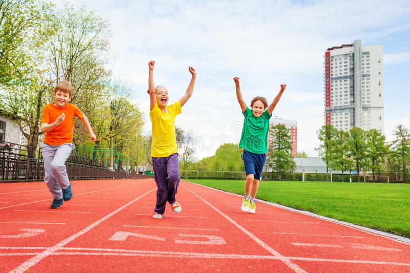Kids in colorful uniforms with arms up running royalty free stock images