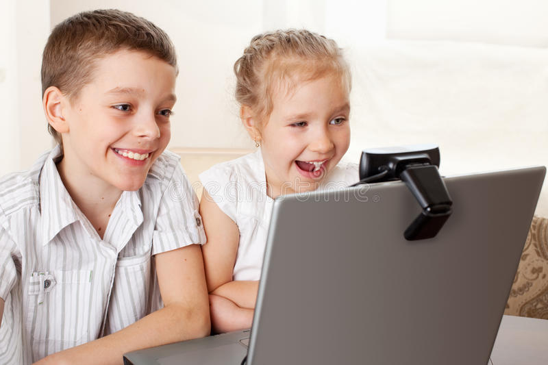 Kids communicate with online. Khildren communicate with online. Happy kids with laptop at home stock images