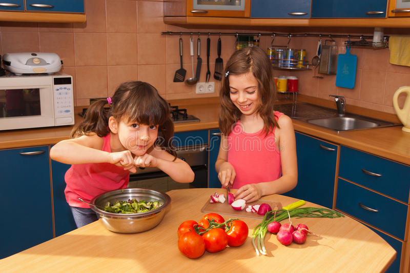 Kids cooking salad at kitchen royalty free stock image