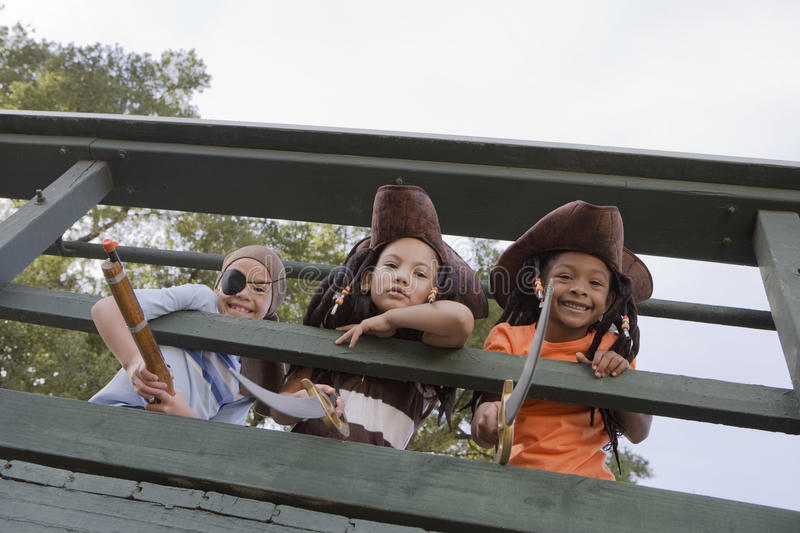 Download Kids In Costumes Looking Through Wooden Railings Stock Photo - Image: 33853242