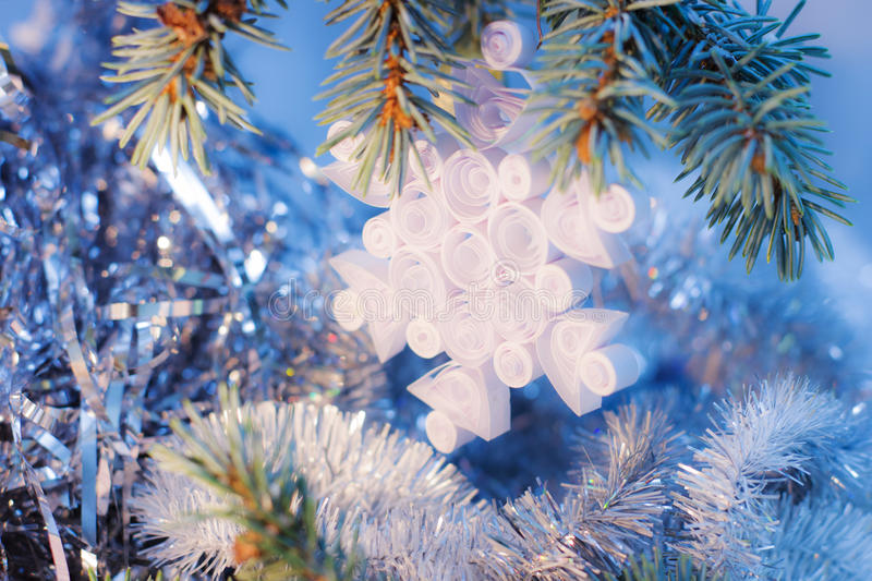 Kids crafts for Christmas. Handmade Christmas gifts toys quilling snowflake from paper vintage on fir tree branches and blue lights bokeh background royalty free stock photography