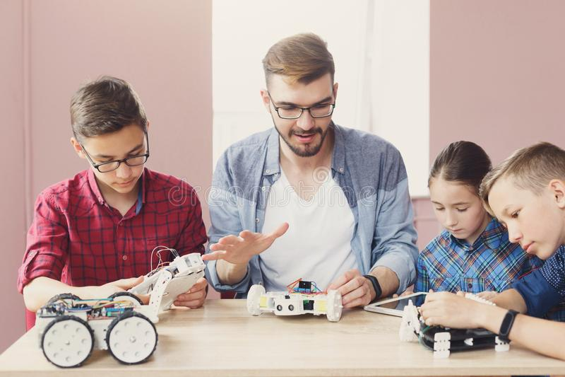 Stem education. Kids creating robots with teacher stock image