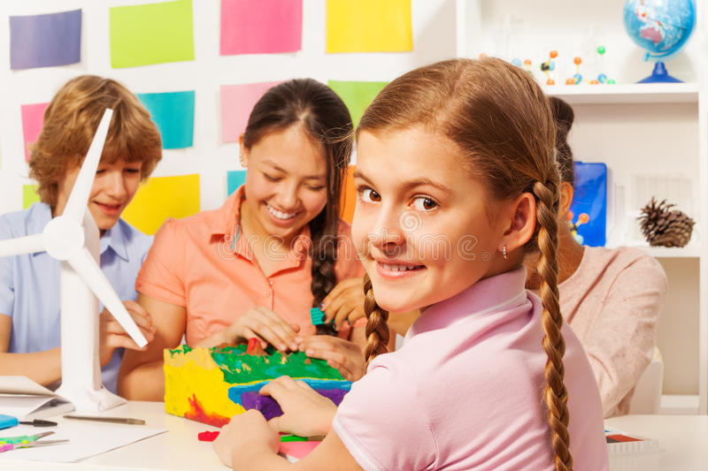 Kids creating surface relief at geography lesson. Teenage kids creating surface relief with modeling clay at the geography lesson stock image