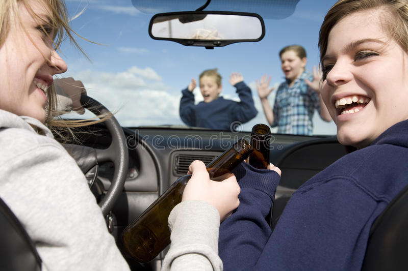 Kids crossing front car drinking. Two teenagers drinking beer and driving a car laughing and not paying attention to the boy and girl that are crossing the stock photography