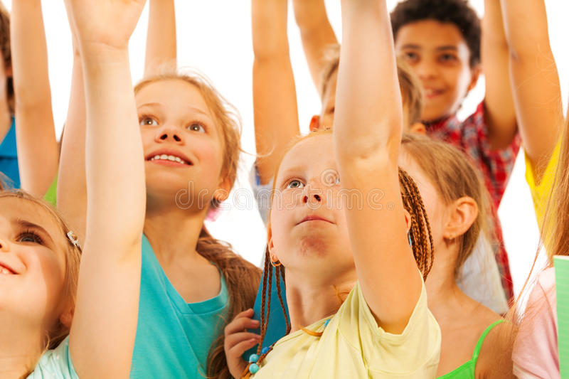 Kids in the crowd smile and rise hands royalty free stock images