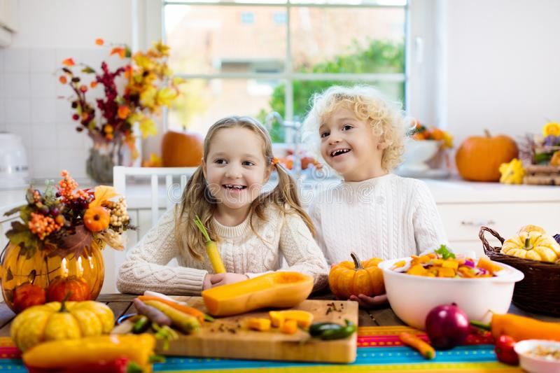 Kids cooking pumpkin soup for Halloween lunch. Kids cutting pumpkin, onion and carrot, cooking soup for autumn meal. Children cook healthy fall vegetables for royalty free stock photos