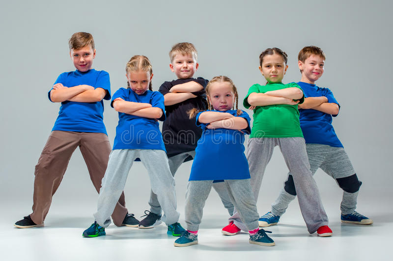 The kids dance school, ballet, hiphop, street, funky and modern dancers. On gray studio background stock images