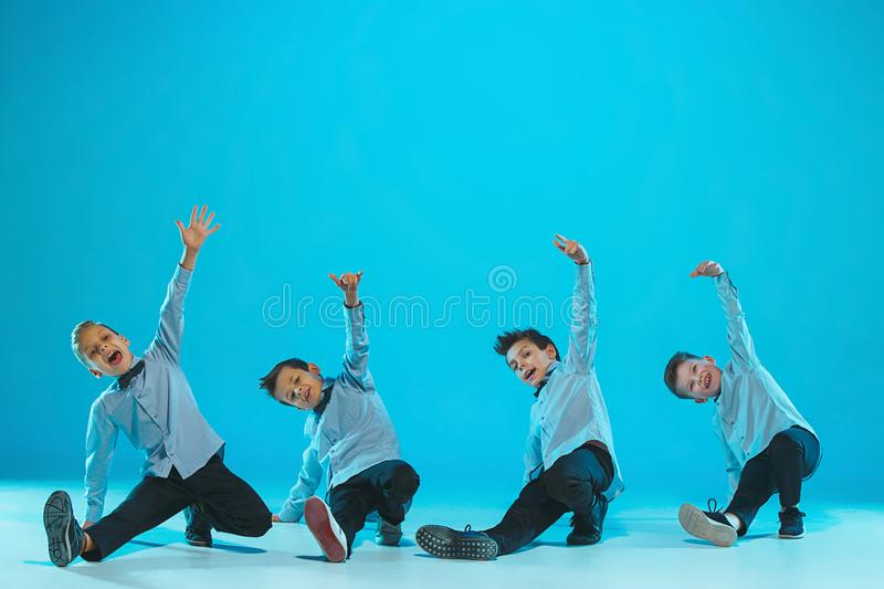 The kids dance school, ballet, hiphop, street, funky and modern dancers. On blue studio background royalty free stock image