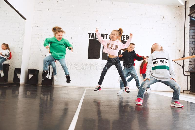 The kids at dance school. Ballet, hiphop, street, funky and modern dancers. Over studio background. Children showing aerobic element. Teens in hip hop style stock images