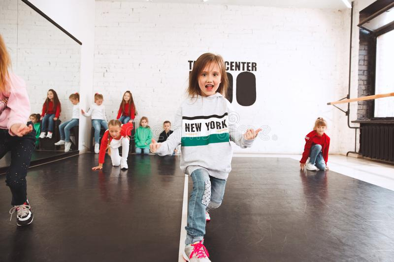The kids at dance school. Ballet, hiphop, street, funky and modern dancers. Over studio background. Children showing aerobic element. Teens in hip hop style stock image