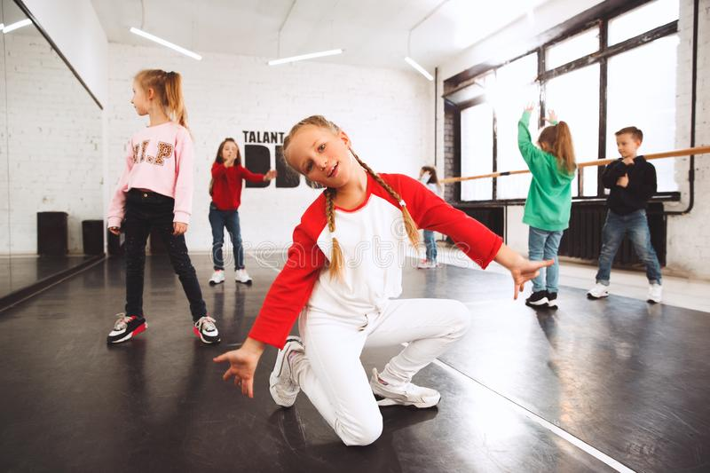 The kids at dance school. Ballet, hiphop, street, funky and modern dancers. Over studio background. Children showing aerobic element. Teens in hip hop style stock photos