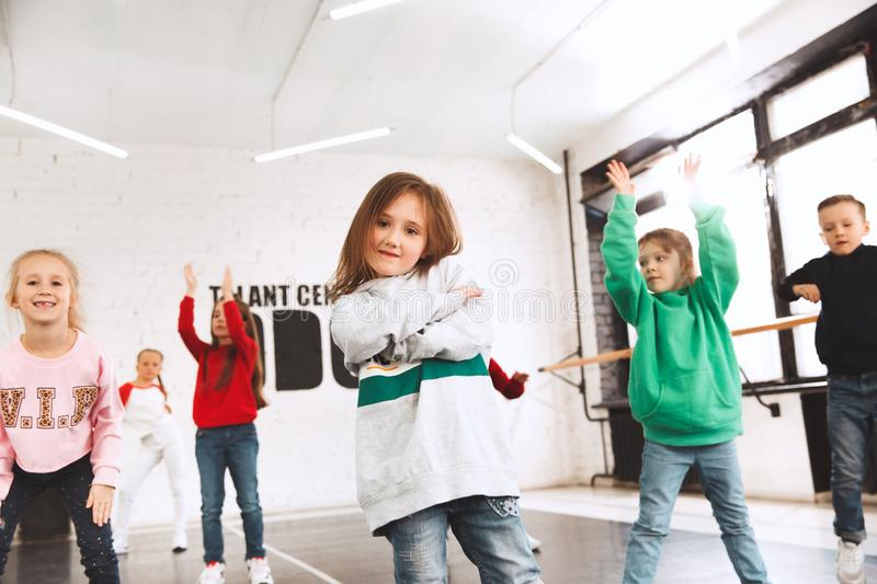 The kids at dance school. Ballet, hiphop, street, funky and modern dancers. Over studio background. Children showing aerobic element. Teens in hip hop style royalty free stock image