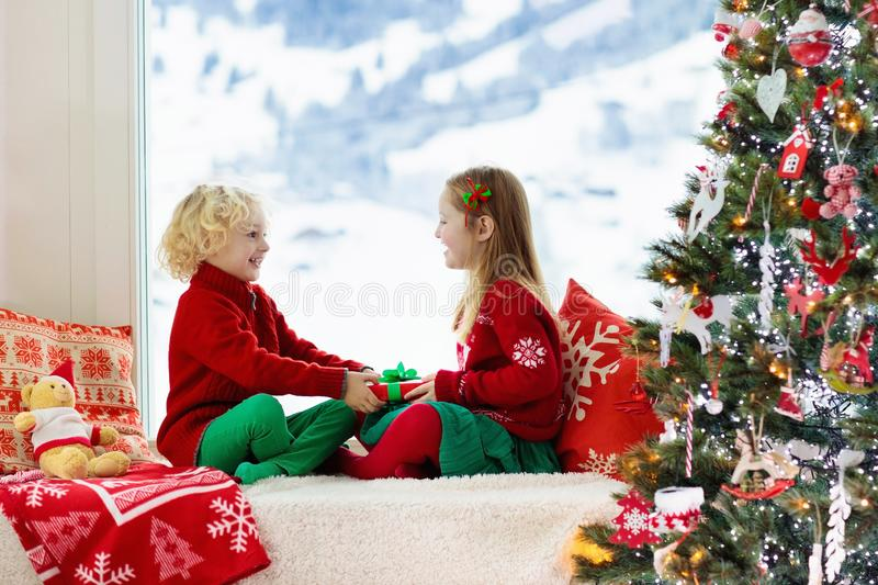 Kids decorate Christmas tree. Child on Xmas eve. Child decorating Christmas tree at home. Little boy and girl in knitted sweater with handmade Xmas ornament royalty free stock photo