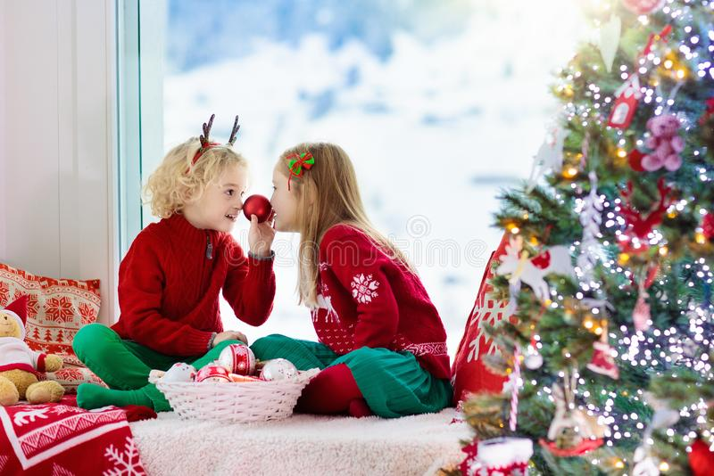 Kids decorate Christmas tree. Child on Xmas eve. Child decorating Christmas tree at home. Little boy and girl in knitted sweater with handmade Xmas ornament stock photos