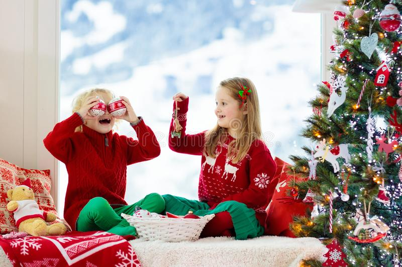 Kids decorate Christmas tree. Child on Xmas eve. Child decorating Christmas tree at home. Little boy and girl in knitted sweater with handmade Xmas ornament stock images
