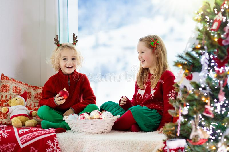Kids decorate Christmas tree. Child on Xmas eve. Child decorating Christmas tree at home. Little boy and girl in knitted sweater with handmade Xmas ornament royalty free stock photography