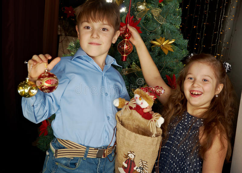 Kids decorate Christmas tree. Happy little kids decorate Christmas tree in beautiful living room with traditional fire place stock photos
