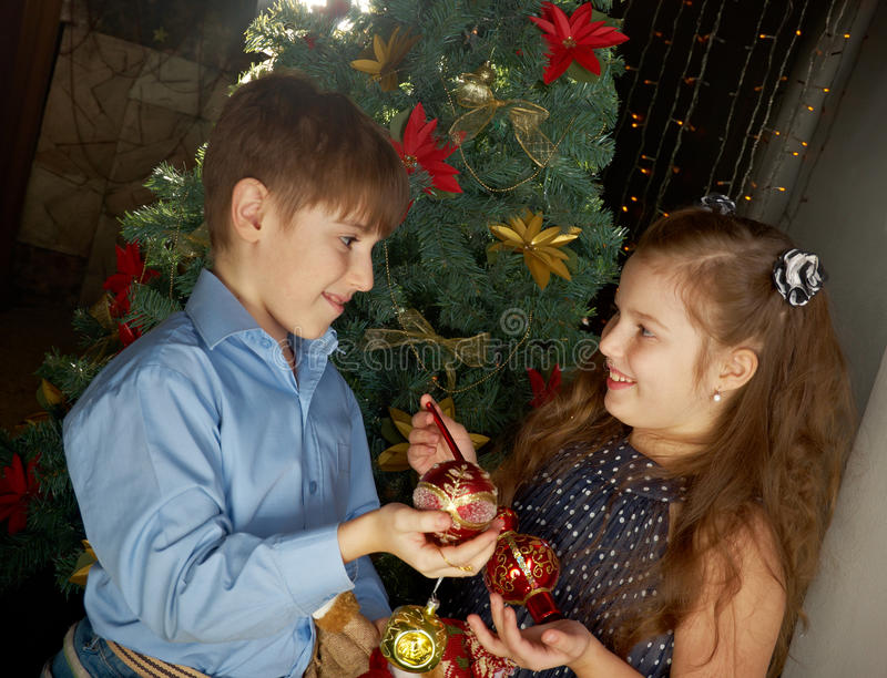 Kids decorate Christmas tree. Happy little kids decorate Christmas tree in beautiful living room with traditional fire place stock photo