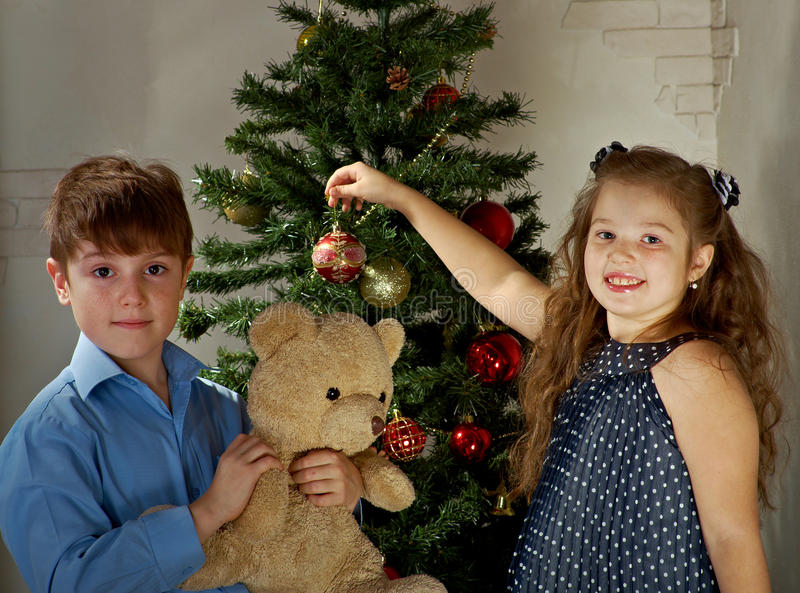 Kids decorate Christmas tree. Happy little kids decorate Christmas tree in beautiful living room with traditional fire place royalty free stock image