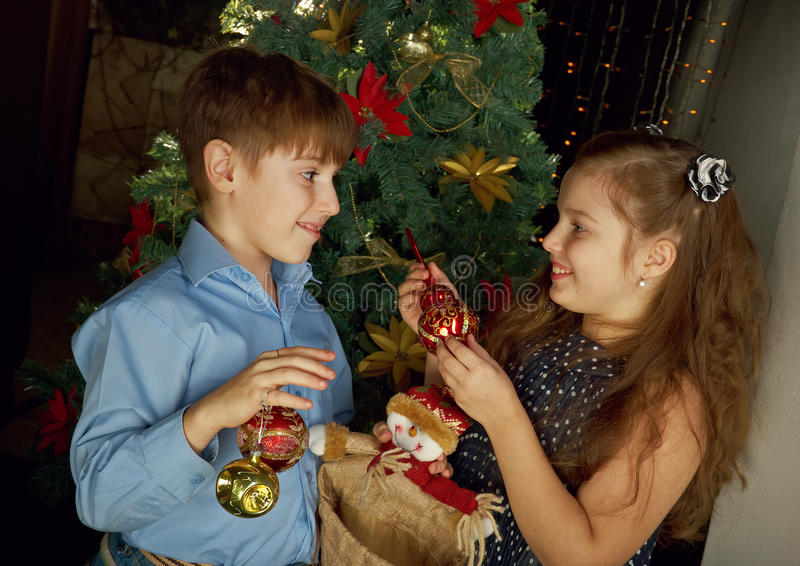 Kids decorate Christmas tree. Happy little kids decorate Christmas tree in beautiful living room with traditional fire place stock photography