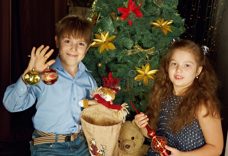 Kids decorate Christmas tree. Happy little kids decorate Christmas tree in beautiful living room with traditional fire place stock image