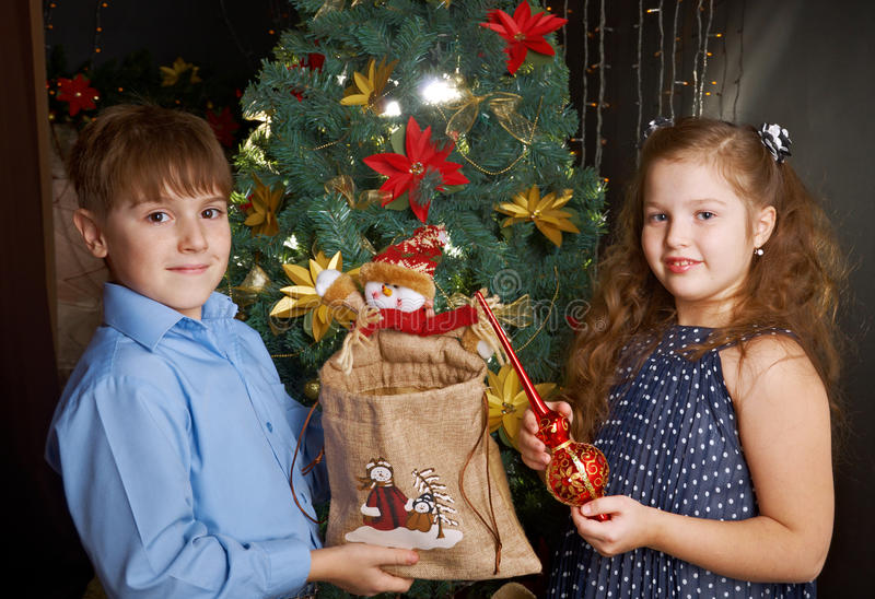 Kids decorate Christmas tree. Happy little kids decorate Christmas tree in beautiful living room with traditional fire place royalty free stock photos