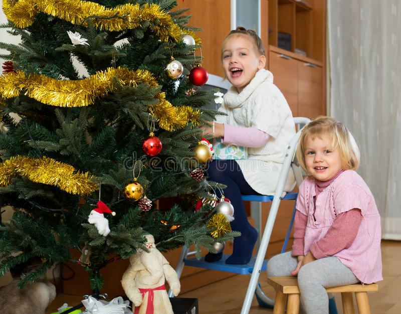 Kids decorate fir for Christmas. Happy smiling kids decorate christmas tree hanging globe ornaments and laughing stock photos