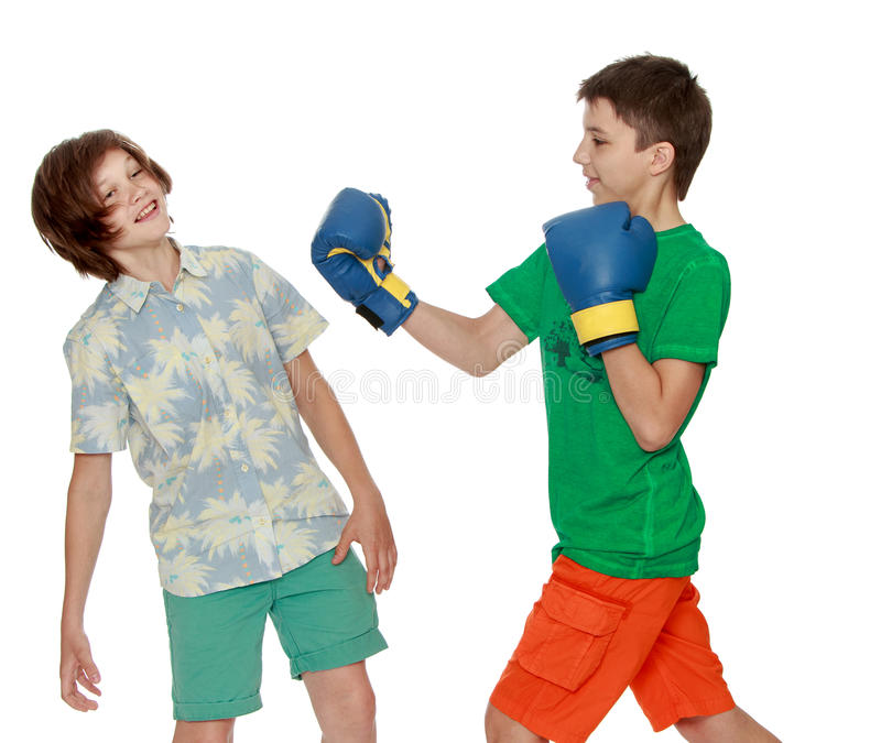 Kids do Boxing in school. Two teenagers imitating a Boxing match-Isolated on white background stock image