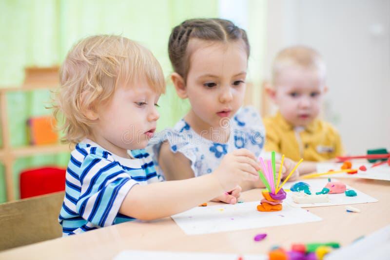 Kids doing arts and crafts in kindergarten stock photo
