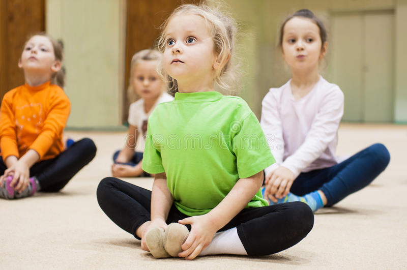 Kids doing exercise in gym stock photos