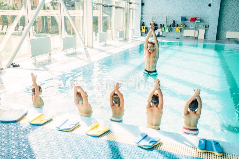 Kids doing exercise in swimming pool stock photos